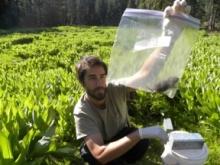 Ryan Kalinowski - in the field holding a specimen rat in a bag