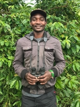 Frank Juma Ong'ondo standing in front of a tree with binoculars in his hands